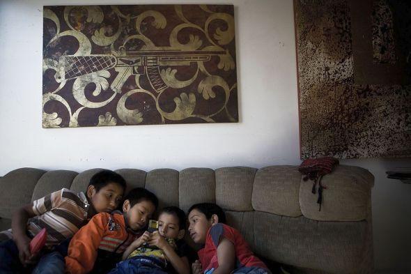 Tepito, México. Además de la Santa Muerte, los niños de Tepito también han empezado a idolatrar sus teléfonos móviles. Foto: Adriana Zehbrauskas.