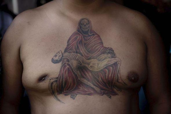 Tepito, México. Un hombre muestra su tatuaje del pecho en honor a la Santa Muerte. Los tatuajes son comunes y son vistos como una ofrenda más. Foto: Adriana Zehbrauskas