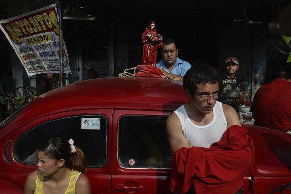 Tepito, México. Los devotos de la Santa Muerte se paran junto a un Vocho rojo (Escarabajo Volkswagen) estacionado fuera del santuario de la santa, esperando la misa mensual en su honor. Foto: Adriana Zehbrauskas.