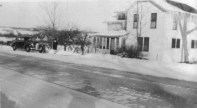 "Winter of 1945: My Sister Earlene in front of Earl's 1941 Chevy. A good view of the house at 826 Frankfort Ave. Tourists often stopped to ask about the ""unusual roof."" Not obvious in this photo was that the gable ends of the roof were cut off or ""hipped"" by a Swiss carpenter named John Weiss whom Earl hired to re-roof the place while Pa and Ma visited his mother in Detroit. Pa asked him why he did that and John said, ""So it would look right."" He explained that all the houses where he came from in the Alps were built like that, to reduce snow and ice damage in winter. Ma was furious until tourists started stopping to comment on how unique and stylish it looked. Margaret Davidhizar, who lives there now, painted it black and had the gable ends restored."