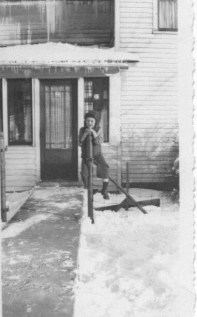 1945 or '46: A good look at the front entrance to the house. That's me, Pat, resting on my laurels (and on the gate post) after shoveling off the walk.