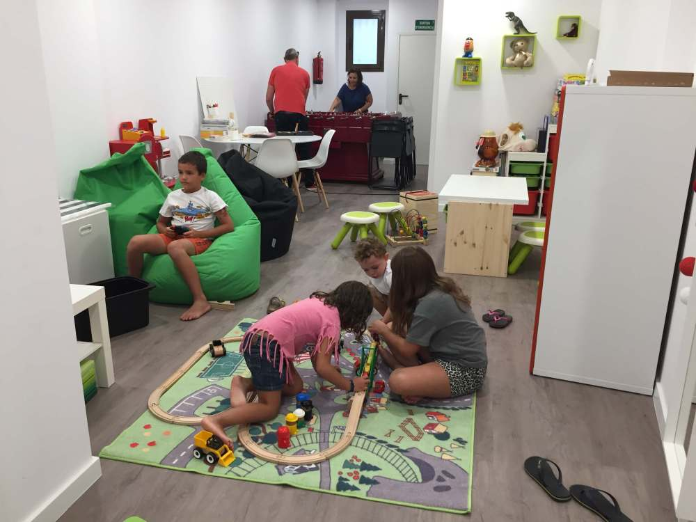 Nens i adults jugant a l'area de jocs.