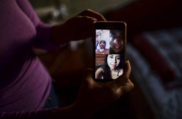 Priscila Almirón muestra una imagen de una videollamada familiar en su teléfono móvil mientras su padre estaba hospitalizado. (Foto de RONALDO SCHEMIDT / AFP).