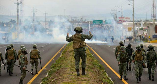 Las fuerzas de seguridad ecuatorianas toman posición durante los enfrentamientos con pueblos indígenas y campesinos que protestan. (Foto: AFP)