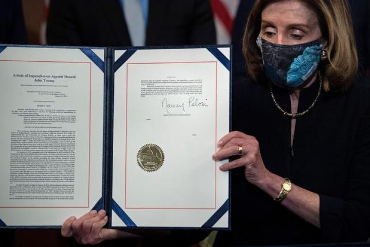 La presidenta de la Cámara de Representantes, Nancy Pelosi, muestra el artículo firmado de la acusación contra Donald Trump. (Foto de Brendan Smialowski / AFP).