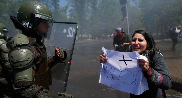 Una manifestante encara a la policía antidisturbios durante una protesta en Santiago. (AFP / Pablo VERA).