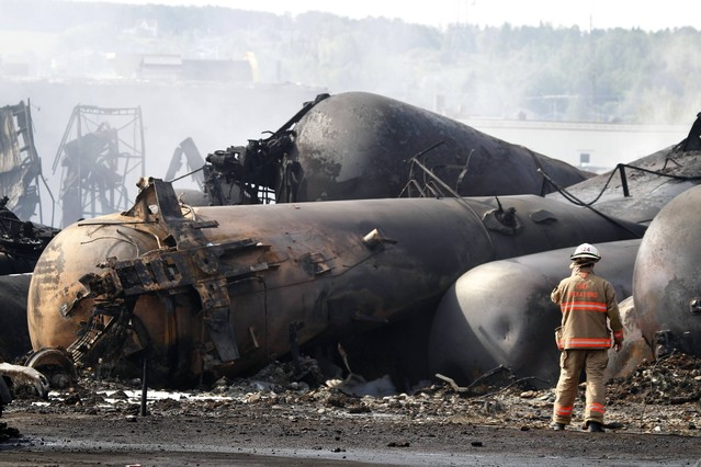 A firefighter works on the scene of a train derailment in Lac Megantic