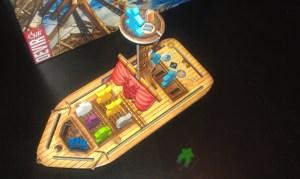 Barco lleno de mercancías y meeple náufrago de referencia (no incluido).