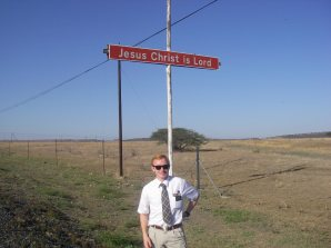 Elder Payne by a sign proclaiming Jesus