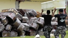 TOPSHOT - Police officers pile empty coffins in one of Ecuador's worst-hit towns, Pedernales, two days after a 7.8-magnitude quake hit the country, on April 18, 2016. Rescuers and desperate families clawed through the rubble Monday to pull out survivors of an earthquake that killed 350 people and destroyed towns in a tourist area of Ecuador. / AFP / RODRIGO BUENDIA