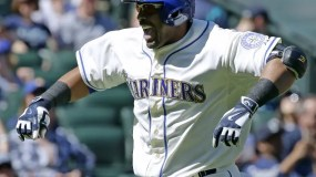 Seattle Mariners' Nelson Cruz celebrates after crossing the plate after he hit a solo home run against the Texas Rangers in the first inning of a baseball game, Sunday, April 19, 2015, in Seattle. (AP Photo/Ted S. Warren)