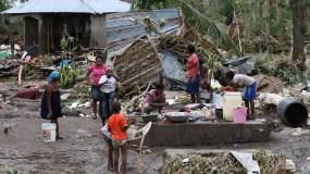 los-efectos-devastadores-del-huracan-matthew-en-haiti-06-10-2016-una-familia-se-reune-en-medio-de-los-escombros-en-les-cayes-haiti-efe