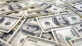 Una parte del dinero cayó sobre la calzada, mientras los hombres forcejeaban.