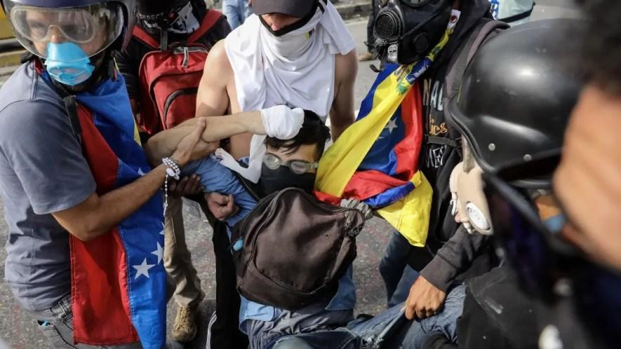 Un grupo de manifestantes auxilia al joven David José Vallenilla (c), de 22 años, luego de recibir un disparo de un miembro de la Guardia Nacional Bolivariana (GNB) hoy,  en las inmediaciones de la bases aérea militar La Carlota, en Caracas (Venezuela). EFE