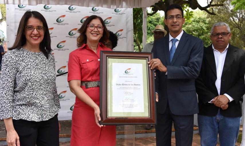 La escritora Dulce Elvira de los Santos recibió el pergamino de la mano del viceministro de Cultura, Juan Morales, en representación del ministro de Cultura, Pedro Vergés.