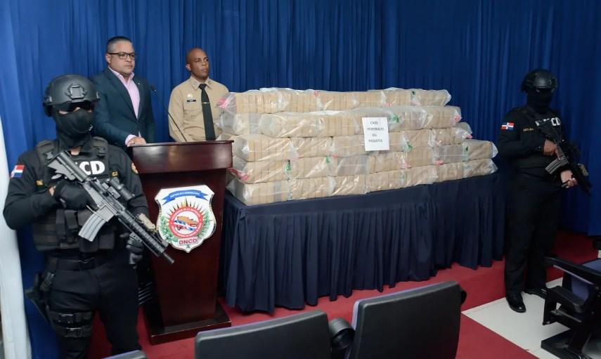 El vocero de la DNCD, Carlos Devers, y el sub director de Relaciones Públicas de la Armada, capitán de corbeta, Daniel Enrique Sosa, muestran a la prensa la droga incautada.