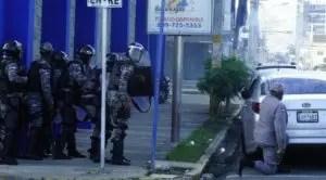 Miembros  de la Policía intentan repeler a los manifestantes.
