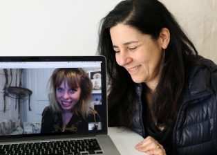 Barbara Weissberger cradles a laptop opened to a skype video call with Eleanor Aldrich smiling