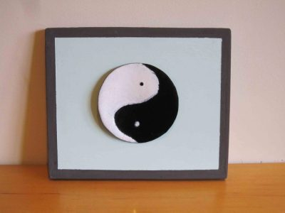 yin yang wall hanging on painted wooden board