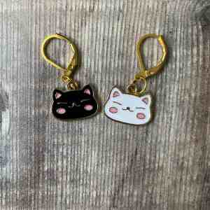 Set of two enamel kawaii cat face stitch markers on a wooden background