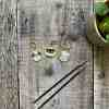 Lifestyle photo of cute dog stitch markers, with knitting needles and part of a plant showing