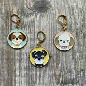 Set of 3 enamel stitch markers or progress keepers for knitting or crochet, on a wood background