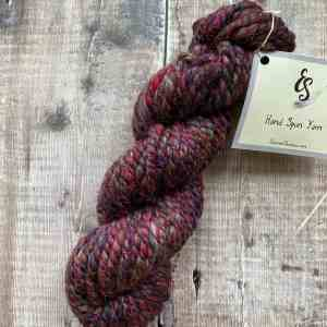 Super bulky hand spun red yarn with red sparkle thread on wood background