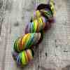 Glorious squishy, bright neon yarn in multicolour on wooden background. Worsted weight, hand spun by Eleanor Shadow in the UK