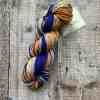Blue, pink, orange and yellow hand spun yarn on wood background, by Eleanor Shadow