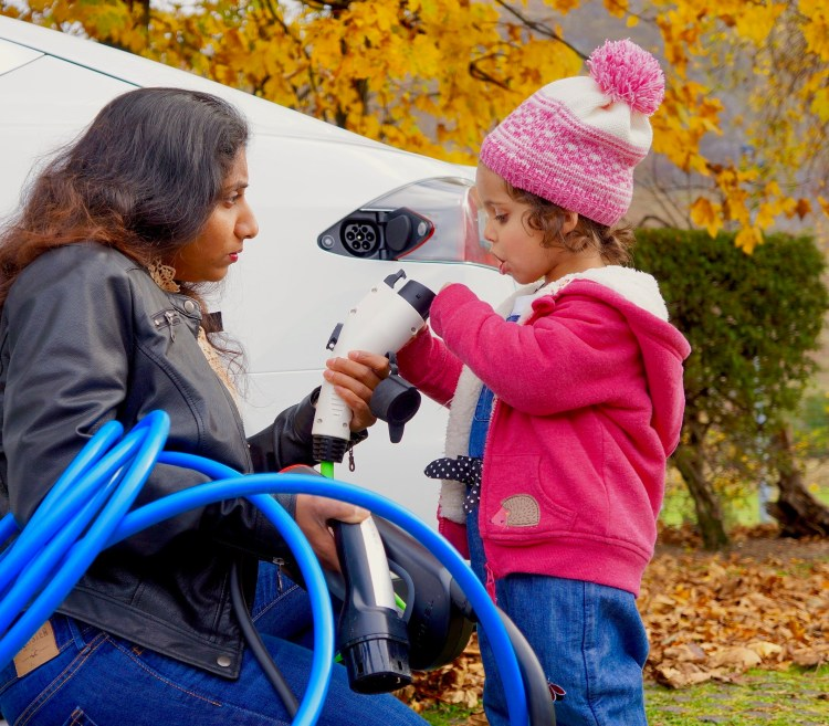 Young girl with mother plugging in electric car