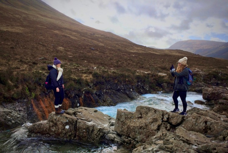 woman standing at fairy pools Skye taking photo of her friend