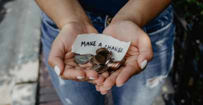 """Hands holding coins and a note that says """"Make a change"""""""