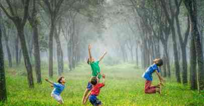 Four boys playing on green grass