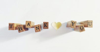 """""""Thank You"""" spelled out with wooden blocks and a paper heart between the two words."""