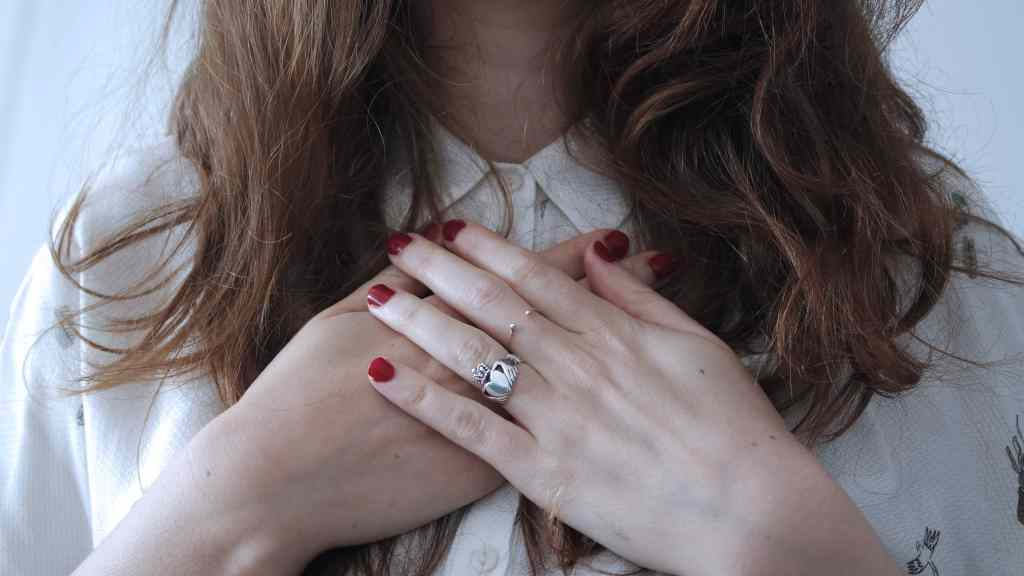 A woman with brown hair holds both of her hands and over her heart.