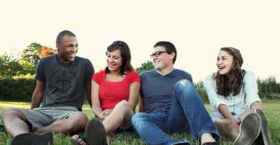 Four friends - one black man, a white woman, a white man, and another white woman - sit together in the grass while laughing.