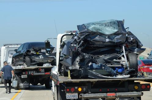 A damaged Tesla, right, and Honda Civic, sit on tow trucks after a collision in the HOV lane on the northbound 405/22 Freeway in Seal Beach after a fatal traffic accident on Monday. According to CHP, the accident happened when a Chevy Tahoe crossed the double yellow lane and entered the number two HOV lane. The Tahoe rear ended a Tesla which was pushed in to a Honda Civic. Two young girls were in the back seat of the Tesla. A 7-year old was killed and a 13-year old was injured and is in critical condition. ///ADDITIONAL INFORMATION: Slug: TrafficFatailty.0816.jag, Day: Monday, August 15, 2016 (8/15/16), Time: 10:58:20 AM, Location: Seal Beach, California - Traffic Fatality - JEFF GRITCHEN, STAFF PHOTOGRAPHER
