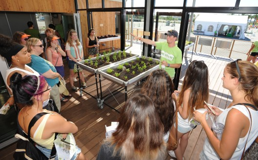 Nate Heckman (center) of University at Buffalo, The State University of New York gives a tour of the GRoWlarium, which utilizes a solarium and a green house into the living quarters of their home at the U.S. Department of Energy Solar Decathlon at the Orange County Great Park, Irvine, California Saturday, Oct. 10, 2015. (Credit: Thomas Kelsey/U.S. Department of Energy Solar Decathlon)