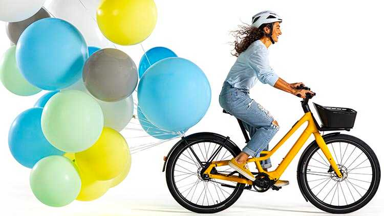 Man with balloons on yellow Specialized Como SL E-Bike