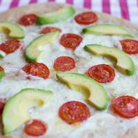 Pizza with avocado and fresh tomatoes