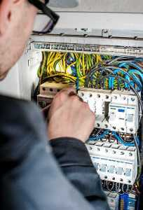 A License Electrician from Singapore Removing an electrical circuit panel for electrical safety regulation inspection.