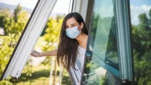 Aire acondicionado y COVID-19. Foto de una mujer con barbijo abriendo una ventana.