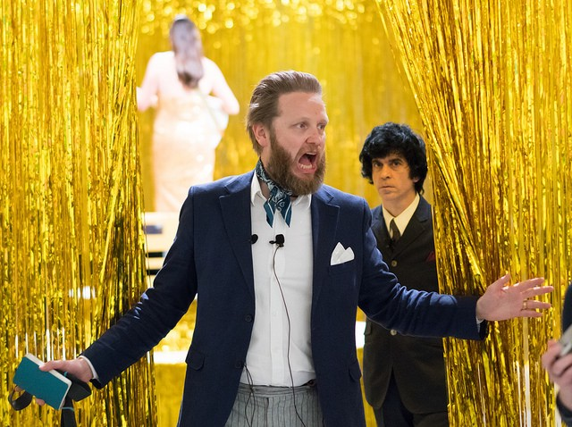Artist Ragnar Kjartansson, a bearded white man, surrounded by gold tinsel, looking like he's shouting. He's wearing a navy suit jacket with a kerchief around his neck.