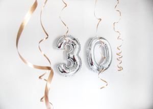 """Silver balloons spelling out """"30"""" and gold streamers"""