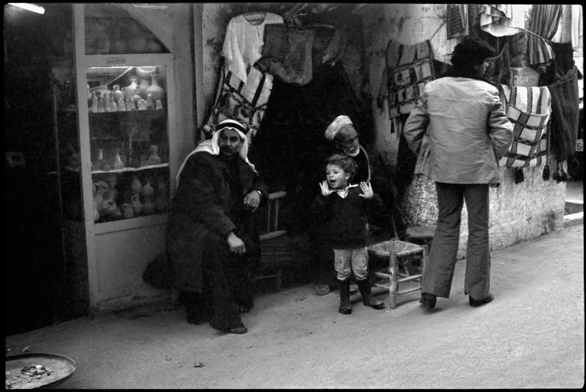 Boy stands next to two men sitting outside souvenir shops