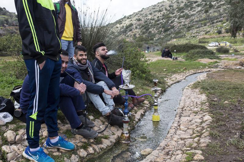 Young men smoking shisha at stream