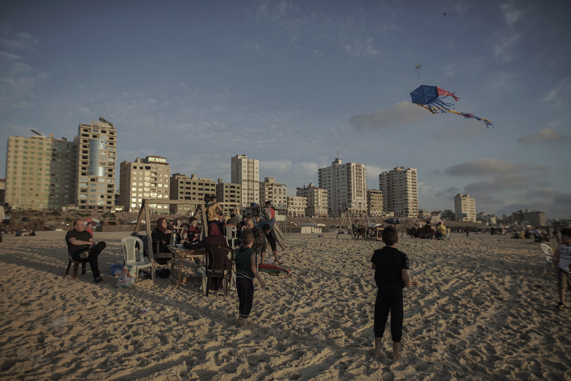 Children play with kites and adults watch as sun goes down over Gaza beach