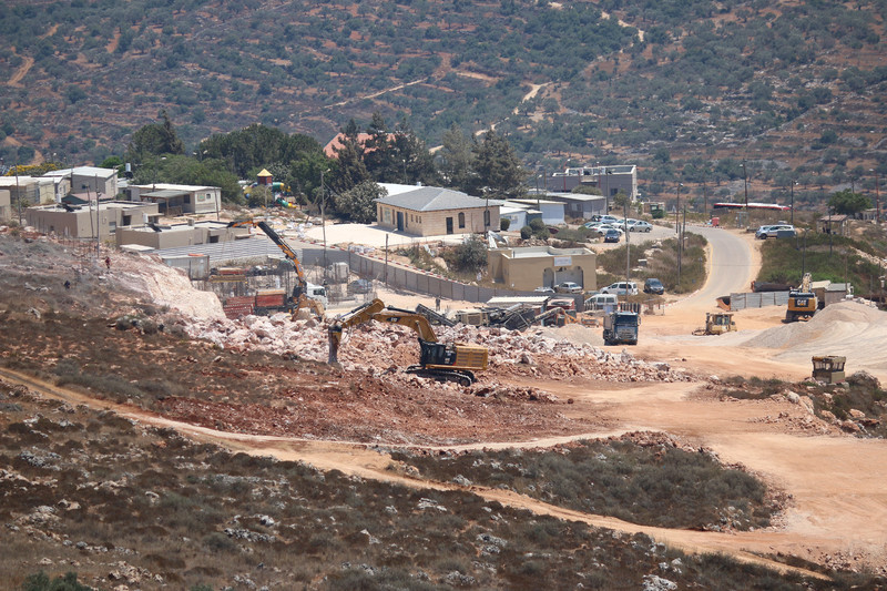 Bulldozer builds structure on open land