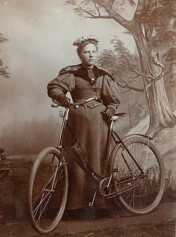 старинная студийная фотография девушки с велосипедом