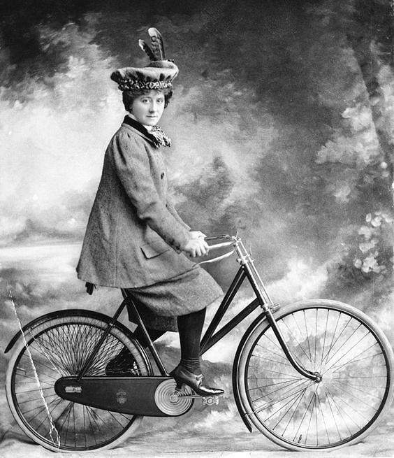 старинная студийная фотография девушка и велосипед